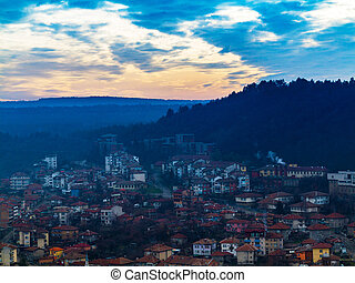 Fantastic beautiful cityscape at dusk with the horizon line disappears in the fog. Image shows a nice grain pattern at 100 percent . At sunset, Veliko Tarnovo , Bulgaria.