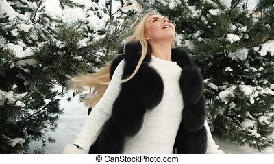 Fantastic blonde is turned against background of snow covered pines.