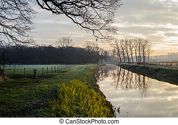 Fantastic calm river with fresh grass in the sunset. Beautiful green winter landscape on a cold day in the morning in the Netherlands