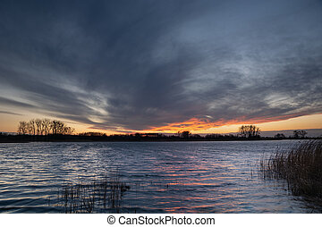 Fantastic clouds on the sky after sunset over a calm lake