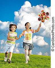 Fantastic scene of happy children running and playing carefreely on green meadow in nature