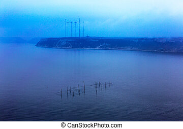 Fantastic seascape network of fishermen with the horizon line disappears in the low fog. Image shows a nice grain pattern at 100 percent. Minimalism.