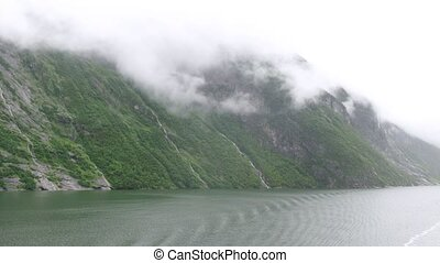 Fantastic waterfalls in misty fjord, time lapse