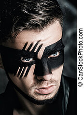 fantasy art makeup. man with black painted mask on face....