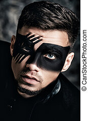 fantasy art makeup. Young man with black painted mask on...
