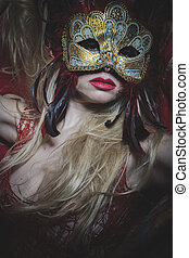 Fantasy, Blonde with gold mask on red cloth embroidered golden thread, mystery and sensuality