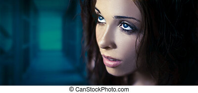 Fantasy glamour portrait of a young beauty with blue eyes