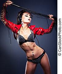 Fantasy. Sexy stripper dj in nightclub with lash. Erotic pose