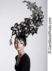 Fantasy. Surrealism. Amazing Woman in Trendy Headwear with Flowers
