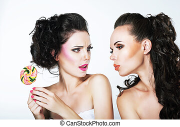 Fantasy. Woman Teasing another with Lollipop