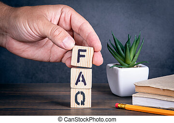 FAQ FREQUENTLY ASKED QUESTIONS. Wooden blocks and a man's hand. Books, pencil and green plant