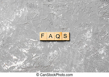 faqs word written on wood block. faqs text on table, concept