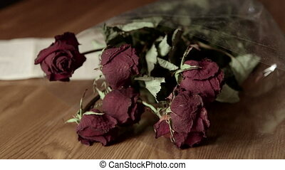 Farewell letter with faded rose bouquet on wooden table
