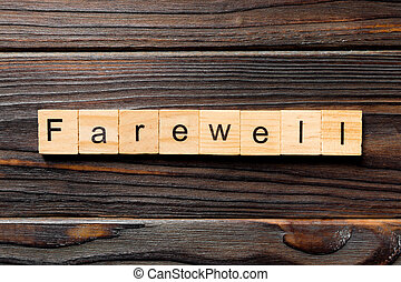farewell word written on wood block. farewell text on table, concept