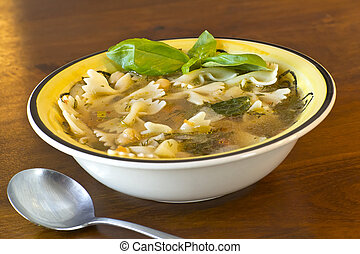 Farfalle bow tie pasta vegetarian soup garnished with fresh basil leaves