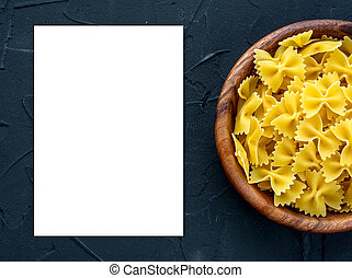 farfalle macaroni pasta in a wooden bowl on a black textured background from the side. Close-up with the top. White space for text and ideas.