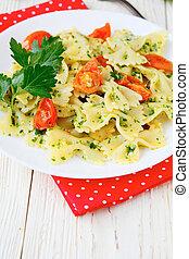 farfalle pasta with pesto and tomato, food closeup