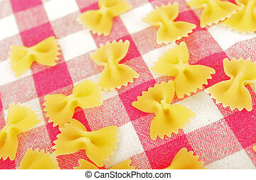 Raw pasta: farfalle on the checkered tablecloth.