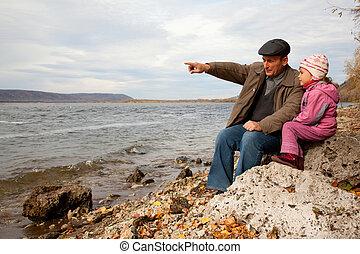 farfar, och, sondotter, sitta, på, sten, och, se, insjö