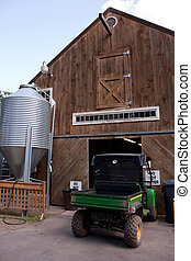 Farm Barn and Equipment - A brown wooden barn with a large...