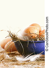 Farm eggs in blue bowl with straw