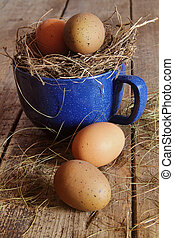 Farm eggs in blue cup with straw