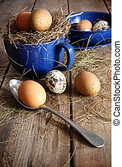 Farm eggs in blue enamel cup and spoon