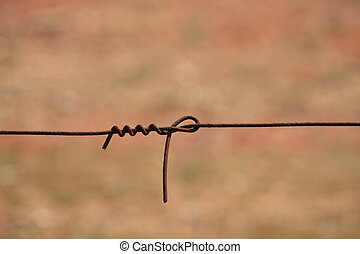 Farm Fencing Wire - Farm fencing wire looped in a knot with...