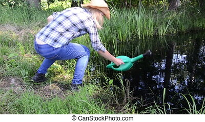 farm girl watering-can - Farm gardener girl draw water from...