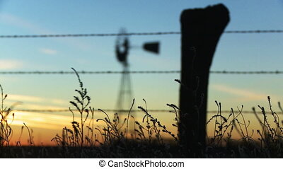 Rack focus from some grass and a barbed wire fence in the foreground to a old fashioned windmill in the background during sunset.