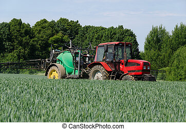 farm machinery tractor long sprayer work in field - farm...