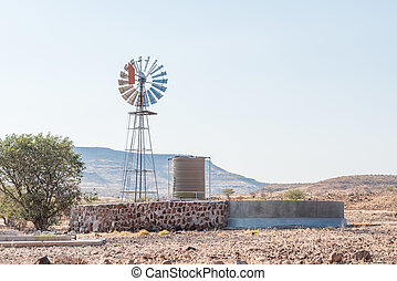 Farm scene with water-pumping windmill and dam at Bergsig