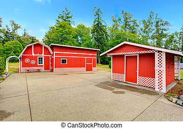 Farm style storage sheds in bright red color with white trim