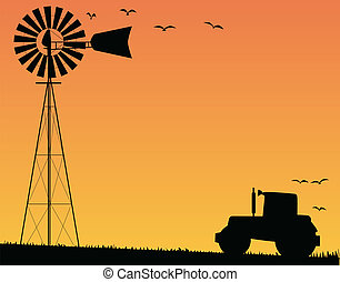 A small water pump windmill and a farm tractor silhouetted by sunset.