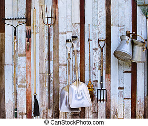 farm tool pitchfork and two shovels against old wooden wall...
