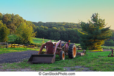 A vintage farm tractor rests in a field with rolling rolling hills, trees, fences, and horses in the background.