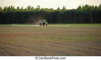 farm tractor fertilize spray wheat field with sprayer from pesticide herbicide