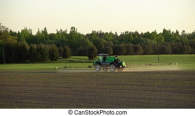 farm tractor spraying fertilize wheat field with sprayer from herbicide