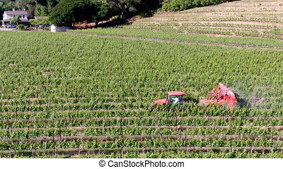 Farm tractor spraying pesticides and insecticides herbicides over green vineyard field.