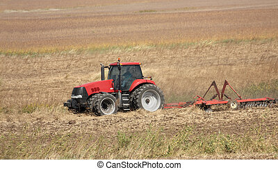 Farm Tractor - Red farm tractor discing a farmfield after...