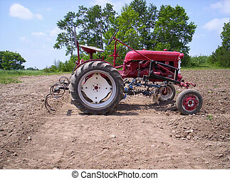 farm tractor - tractor is used to cultivat weed around new...