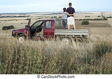 An Australian farmer and his wife stop to take in the view from the back of the 'ute'.