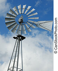 farm windmill water pump against blue sky with clouds