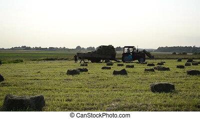 farm worker load hay bale