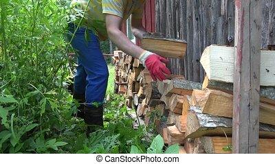 Farm worker man boy unload firewood wood from rusty...