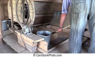 farm worker sift grain