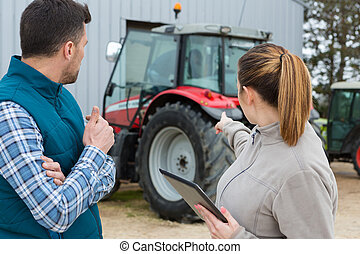 farmer and co-worker pointing at tractor