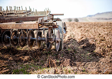 Farmer and tractor with plough, plowing in a field