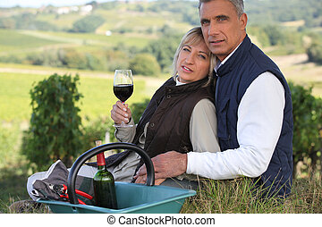 Farmer and wife drinking wine in a vineyard