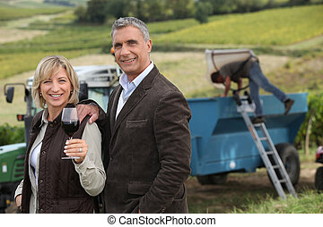Farmer and wife in front of equipment